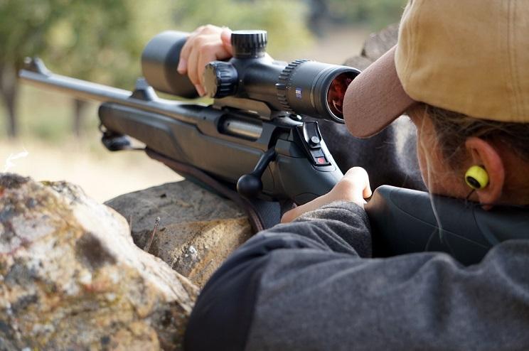 apuntando con el rifle mirando por el visor